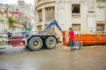 environmental sanitation: HAVANA, CUBA - DECEMBER 2, 2013: Waste collection vehicle picking up garbage container from the streets