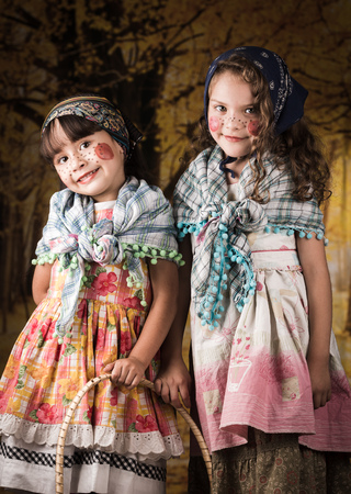 Cute little girls dressed as a traditional witches with colorful dresses and headscarves
