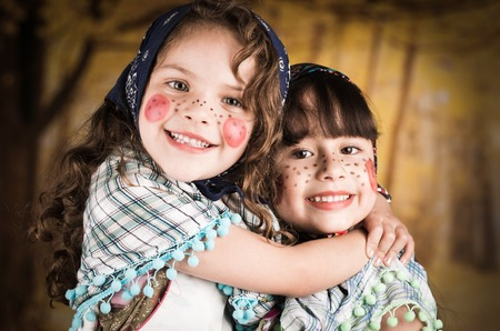 costumes: Beautiful little girls dressed as a traditional witches hugging each other