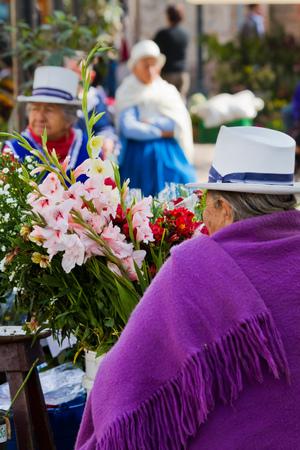 flores: CUENCA, ECUADOR - AUGUST 22, 2010: Indigenous woman selling flowers in Plaza de Flores Square in Cuenca