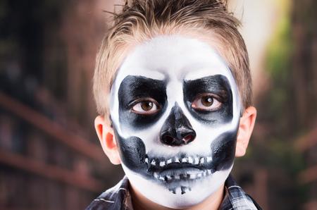 insidious: Tough little boy with skull makeup costume for halloween, closeup