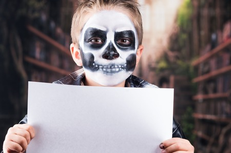 insidious: Close up portrait of young boy with skull make up holding white paper, copy space
