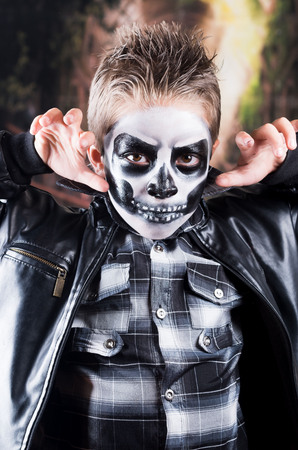 insidious: Scary little boy wearing skull makeup for halloween using fingers to scare