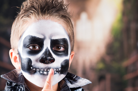 Scary little boy wearing skull makeup for halloween gesturing silence