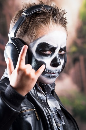 insidious: Close up portrait of young tough rocker boy with skull make up wearing music headphones and black leather jacket and holding rock on sign