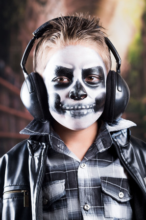 insidious: Close up portrait of young tough rocker boy with skull make up wearing music headphones and black leather jacket
