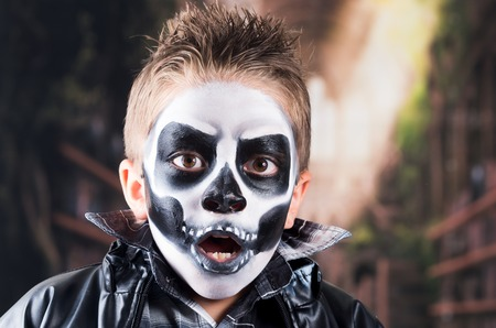 Scary little boy wearing skull makeup for halloween looking scared