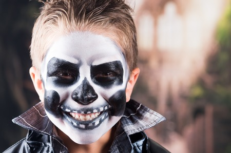 Scary little boy smiling wearing skull makeup for halloween