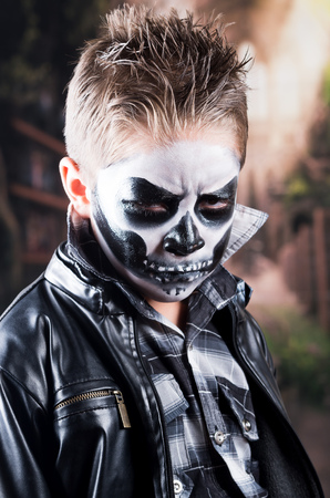 intimidating: Tough little boy with skull makeup costume looking scary