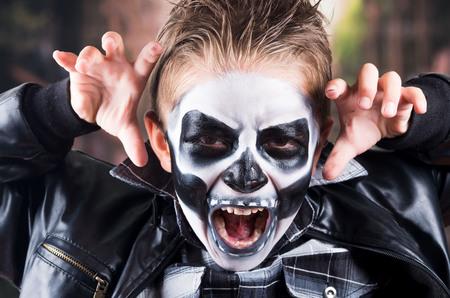 Enge kleine jongen dragen schedel make-up voor Halloween met behulp van de vingers te schrikken