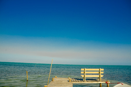 tourism in belize: wooden bench over pier dock jetty with relaxing ocean view caye caulker belize caribbean
