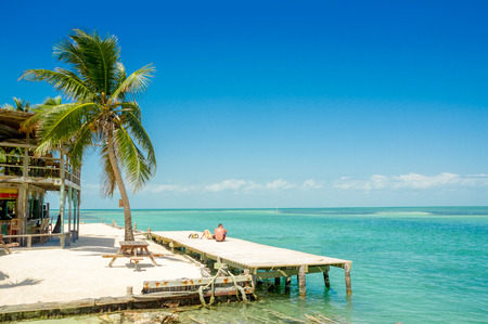 Blissful view of wooden dock above turquoise water in caye caulker belize caribbean Archivio Fotografico