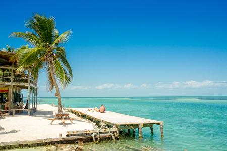 Zalig uitzicht op houten dok boven turquoise water in Caye Caulker Belize caribbean