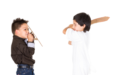 small sword: Two small boys simluating sword fight using toys and homemade shield, white background. Stock Photo