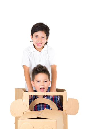 outdoor activities: Adorable young boys playing and sitting in a cardboard car isolated over white background. Stock Photo