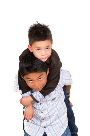 facing on camera: Two small hispanic boys playing, one carrying the other on his back, facing camera. Stock Photo