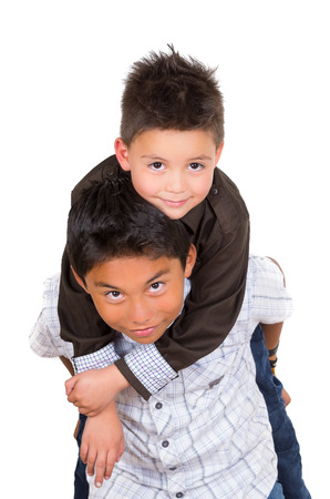 facing to camera: Two small hispanic boys playing, one carrying the other on his back, facing camera. Stock Photo