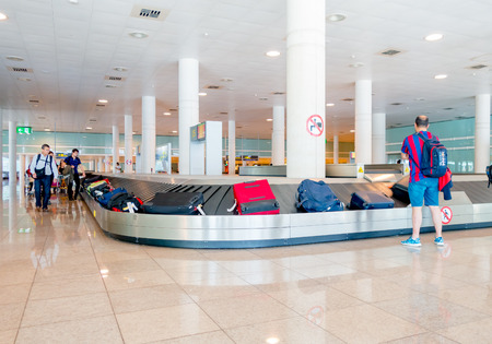 barajas: BARCELONA, SPAIN - 8 AUGUST, 2015: Conveyer belt for arrivals luggage with suitcases and people around waiting inside large bright colored hall at airport.
