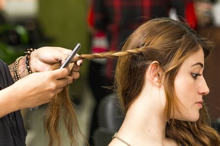 hair stylist: Closeup stylist hands working with brunette hair making a twist. Stock Photo