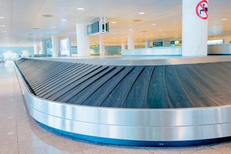 conveyer: BARCELONA, SPAIN - 8 AUGUST, 2015: Conveyer belt for arrivals luggage inside large light colored hall at El Prat airport .