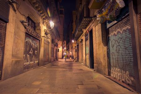 backstreet: BARCELONA, SPAIN - 8 AUGUST, 2015: Picturesque charming Barcelona narrow backstreet, tall grey concrete walls on both sides creates dark atmosphere.