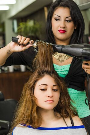 hair stylist: Brunette facing camera getting hair done by professional stylist.