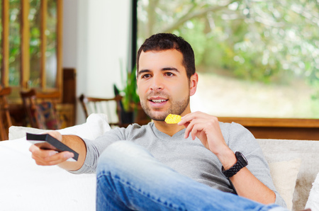 3 persons only: Hispanic male wearing light blue sweater plus denim jeans sitting in white sofa holding potato chip and remote control watching tv enthusiastically. Stock Photo