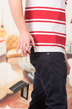 steam mouth: Man wearing red white striped shirt and dark jeans dropping wallet.