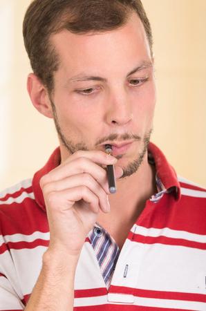 facing to camera: Hispanic man wearing red white striped shirt facing camera smoking on electronic cigarette. Stock Photo