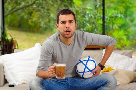 enthusiastically: Hispanic man wearing denim jeans with grey sweater sitting in sofa enthusiastically worried expression watching tv holding beer and football .