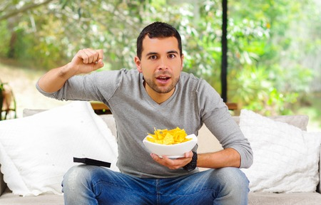 couch potato: Hispanic male wearing light blue sweater plus denim jeans sitting in white sofa holding bowl of potato chips and remote control watching tv enthusiastically.