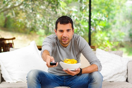 enthusiastically: Hispanic male wearing light blue sweater plus denim jeans sitting in white sofa holding bowl of potato chips and remote control watching tv enthusiastically.