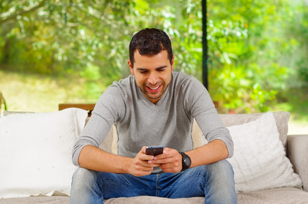 leaning forward: Hispanic man wearing denim jeans with grey sweater sitting in sofa leaning forward looking at phone screen. Stock Photo