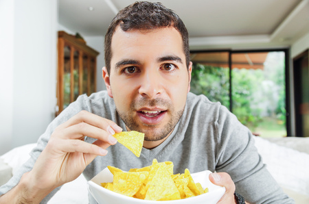 lying on couch: Closeup hispanic male wearing light blue sweater holding up bowl of potato chips in front of camera, funny angle. Stock Photo