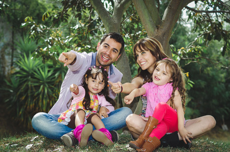 engaging: Beautiful hispanic family of four sitting outside on grass engaging in conversations while posing naturally and happily.