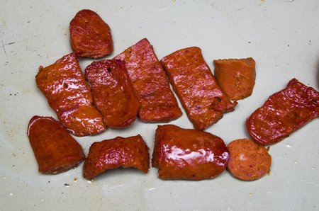 plantain herb: Red colored latin chorizo sausage cut in pieces and lying on white surface. Stock Photo