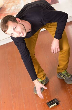 bending down: Man wearing beige jeans and dark sweater smiling towards camera while bending down to pick up wallet from ground.