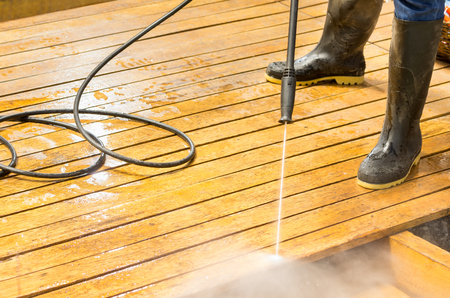 Man wearing rubber boots using high water pressure cleaner on wooden terrace surface. Stock Photo
