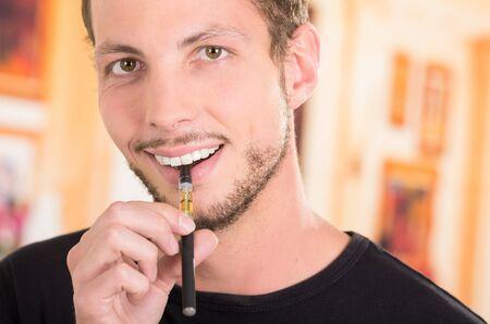 steam mouth: Hispanic man wearing dark sweater enjoying an electronic cigarette while posing for camera. Stock Photo
