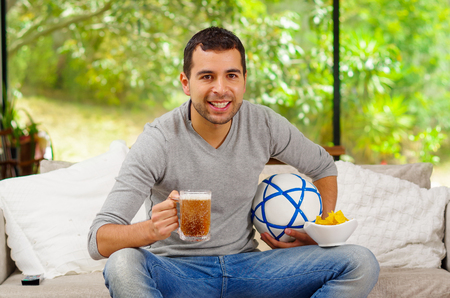 enthusiastically: Hispanic man wearing denim jeans with grey sweater sitting in sofa enthusiastically watching tv holding beer and football.
