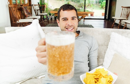facing on camera: Hispanic pleased male wearing light blye sweater enjoying potato chips and beer sitting in white livingroom sofa facing camera.