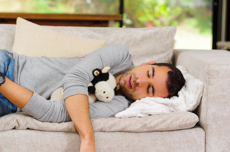couch potato: Hispanic male wearing blue sweater and jeans lying on white sofa with stuffed animal between arms sleeping. Stock Photo