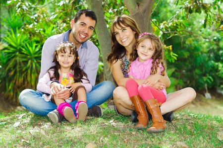Beautiful hispanic family of four sitting outside on grass engaging in conversations while posing naturally and happily.