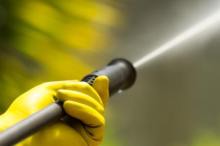 dirty water: Closeup black head of high pressure water cleaner as waterbeam emerges.