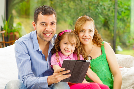 looking towards camera: Family portrait of father , mother and daughter sitting together in sofa holding tablet looking towards camera.