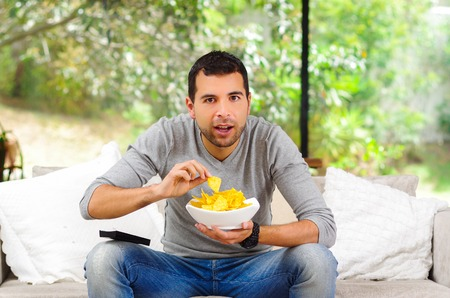lying on couch: Hispanic male wearing light blue sweater plus denim jeans sitting in white sofa holding bowl of potato chips and remote control watching tv enthusiastically.