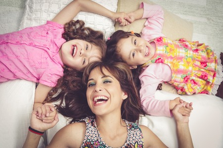 happy families: Young adorable hispanic sisters and mother lying down with heads touching and bodies spread out different directions closeup.