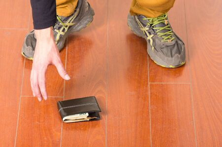 bending down: Man wearing beige jeans and dark sweater bending down to pick up wallet from ground. Stock Photo