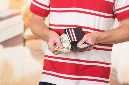 Man wearing red white striped shirt holding wallet with money and cards visible.