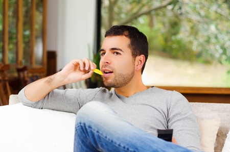 enthusiastically: Hispanic male wearing light blue sweater plus denim jeans sitting in white sofa holding potato chip and remote control watching tv enthusiastically. Stock Photo